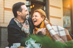 midle-aged couple laughing and leaning into each other at an outdoor cafe